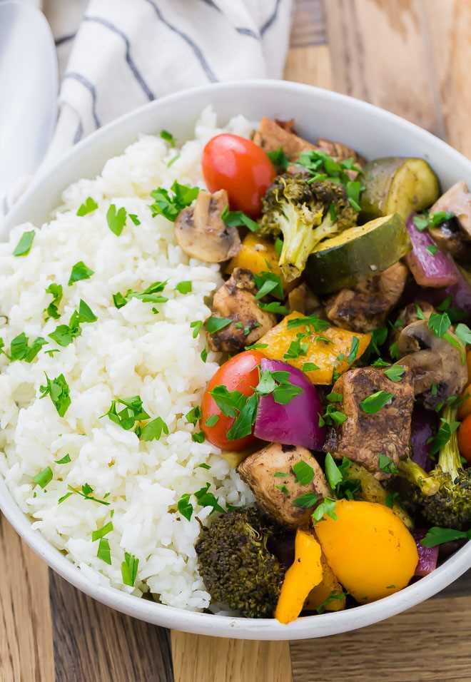 Imagem de um prato de arroz, frango, cogumelos, pimentões, cebola, abobrinha, brócolis e tomate. Esta refeição é decorada com salsa fresca.