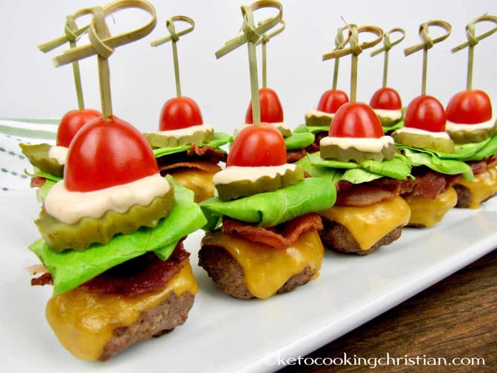 mini hamburguesas con lechuga con tocino, tomate y aderezo mil islas con un pincho en el centro