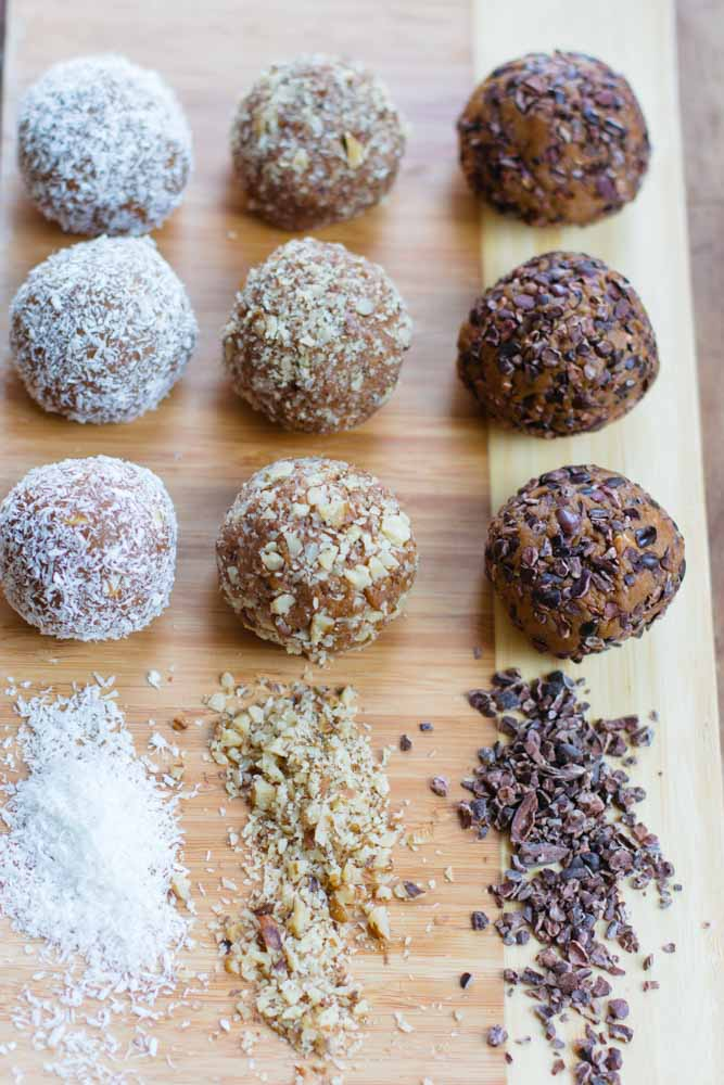 Three types of unbaked pumpkin balls: coconut, nuts, and chocolate