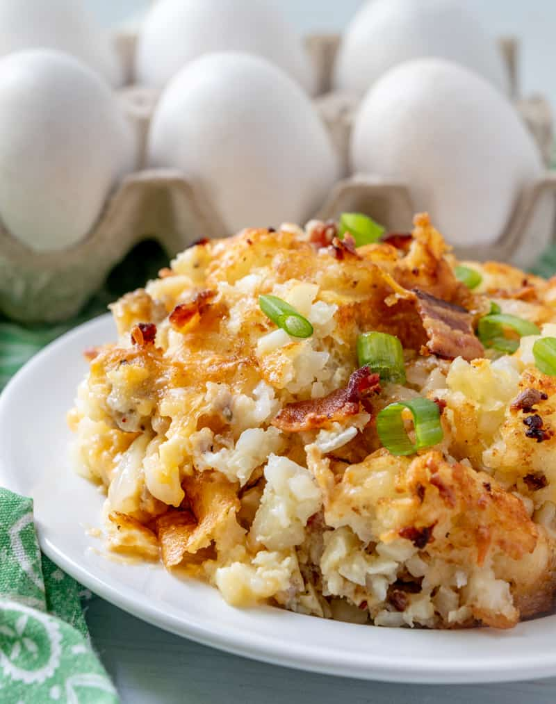 Feche acima do tiro da caçarola em um prato com cebola verde e queijo com os ovos no fundo.