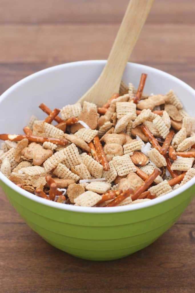 Un tazón lleno de cereal Chex, graham de peluche, palitos de pretzel, almendras y coco con una cuchara de madera también.