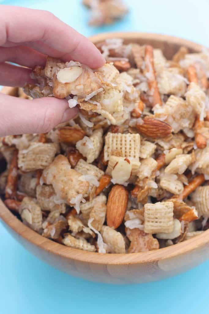 Una mano metiendo la mano en un tazón para agarrar una pizca de mezcla de almendras y coco Chex.