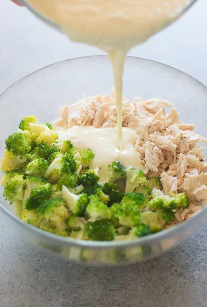 Pollo desmenuzado y brócoli al vapor en un tazón con salsa alfredo encima.