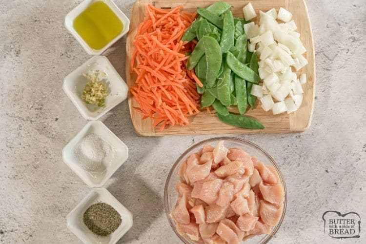 tazón de aceite de oliva, ajo, sal, pimienta, pollo, guisantes, zanahorias y cebolla