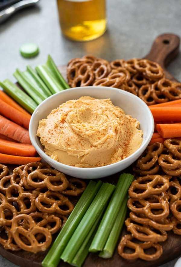 Cerca de la receta de queso pub con pretzels, zanahorias y apio alrededor