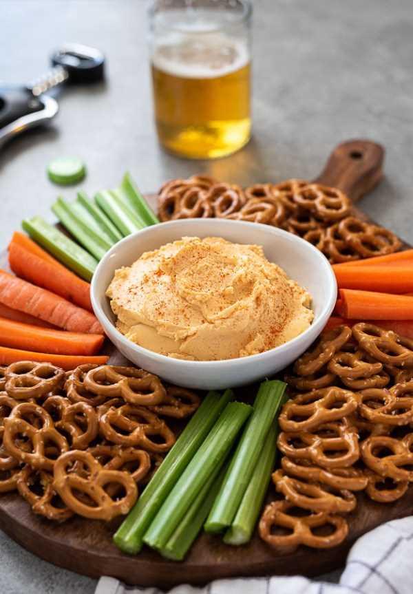 servidor de madera con tazón de queso pub y pretzels, zanahorias y apio