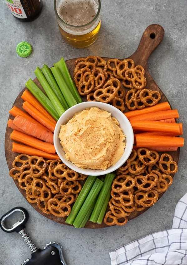 Toma cenital de plato de queso pub con zanahorias, apio y pretzels