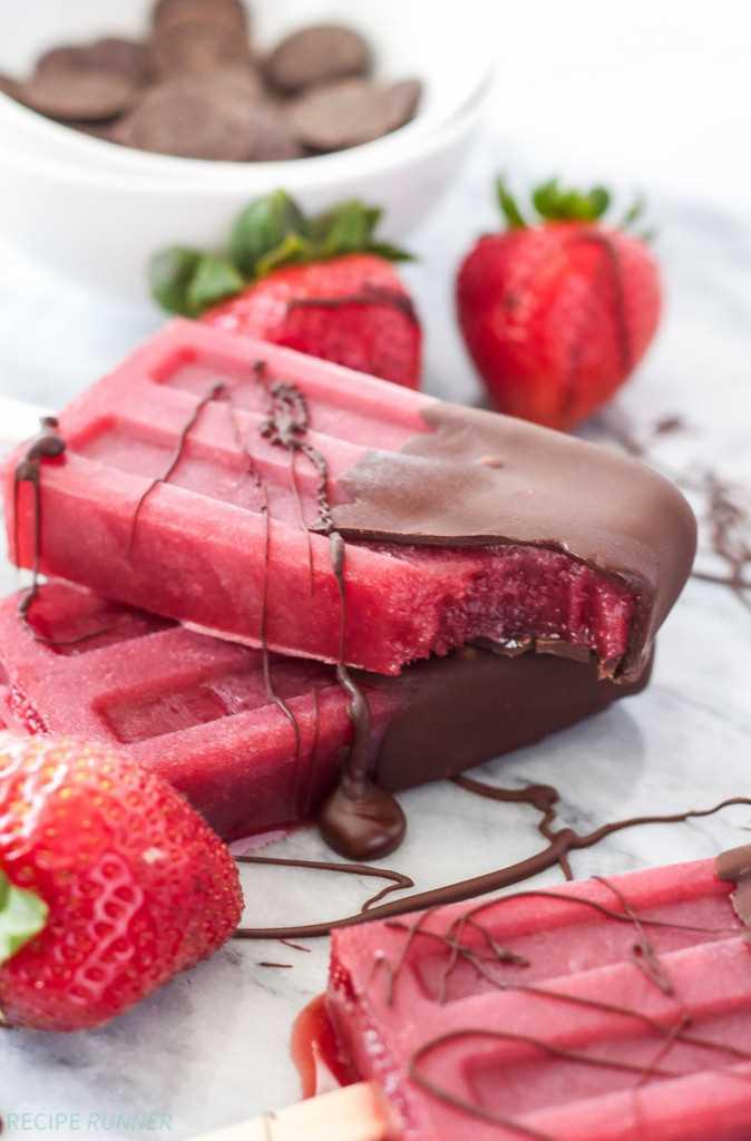 Fresas bañadas en chocolate Vino tinto Paletas sobre tabla de cortar de mármol con fresas frescas al lado.