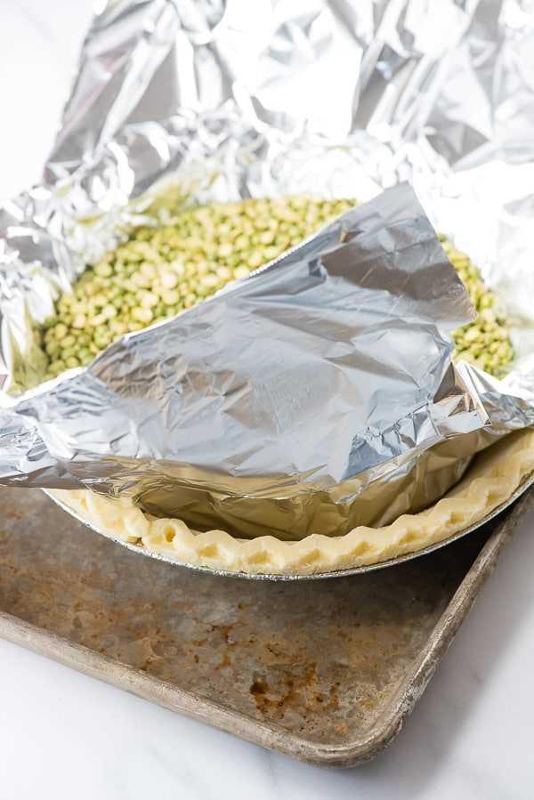 Crosta de bolo sem glúten congelada em uma assadeira com papel alumínio e feijão por dentro para uma crosta cega