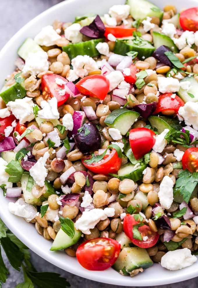 Salada mediterrânea de lentilha em uma tigela branca. Feito com lentilhas, pepinos, tomates, azeitonas, queijo feta e ervas.