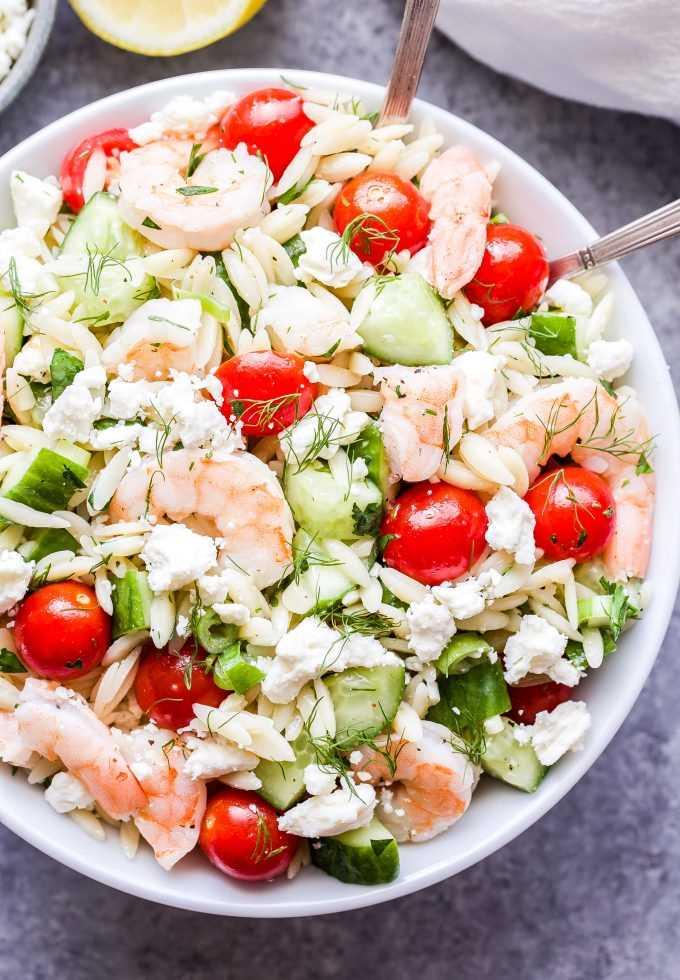 Salada de camarão Orzo com queijo feta e ervas com colheres em uma tigela branca.