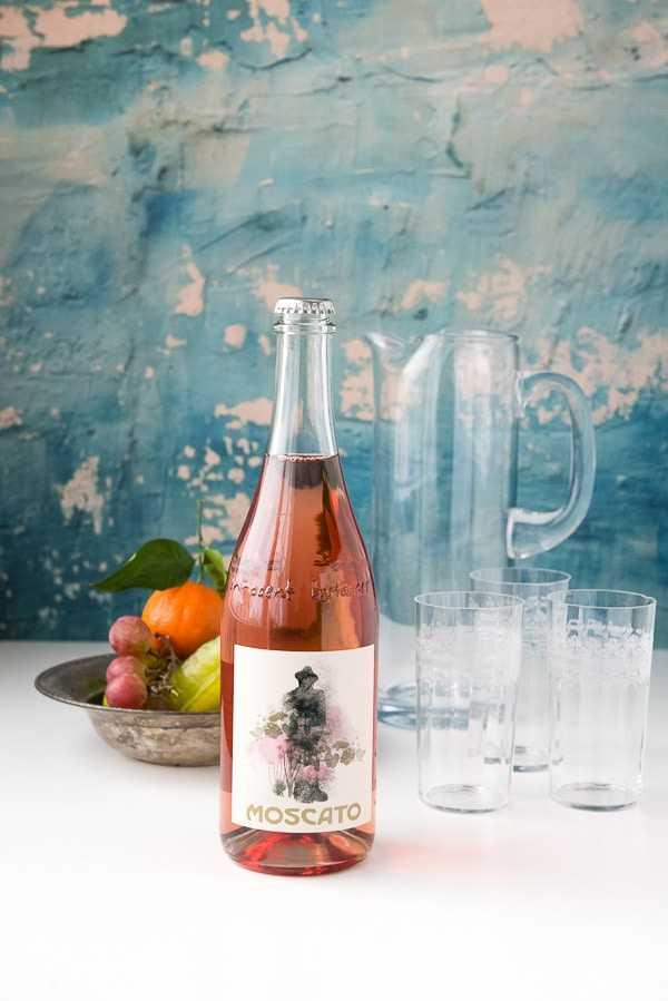 Garrafa de vinho de Moscato, jarro vazio e copos altos, juntamente com uma tigela de frutas frescas para fazer coquetéis de sangria de Moscato