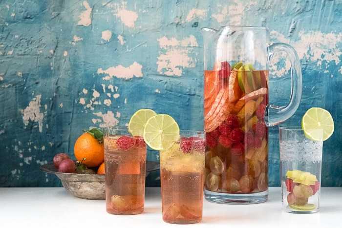 mesa de festa com uma jarra alta de sangria de vinho moscato cercada por copos individuais da sangria de vinho