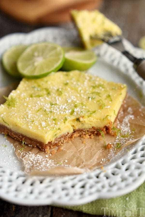 barras de limón con azúcar en polvo y ralladura en un plato blanco