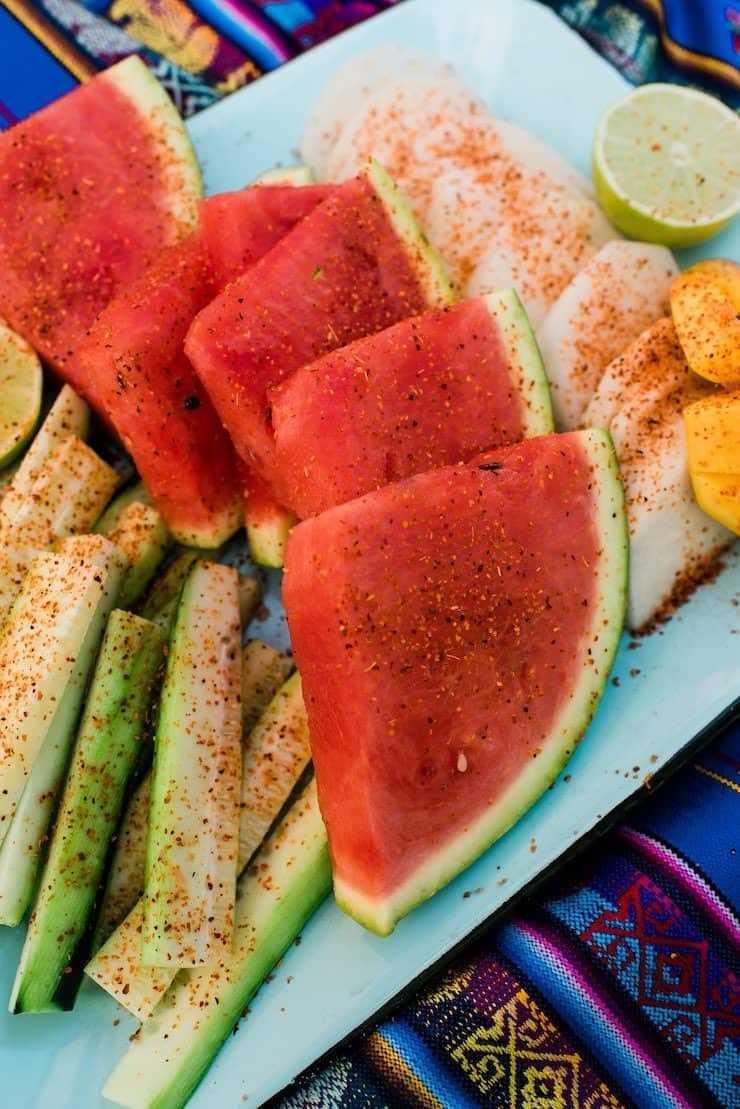 rodajas de fruta espolvoreadas con chile en polvo en un plato verde azulado en un corredor mexicano