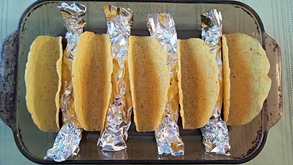 "4 rollos de papel de aluminio en una fuente para hornear con 5 conchas de taco entre ellos ""srcset ="" https://cdn1.zonacooks.com/wp-content/uploads/2017/08/Smoky-Pulled-Pork-Tacos-Recipe- for-Two-3.jpg 1000w, https://cdn1.zonacooks.com/wp-content/uploads/2017/08/Smoky-Pulled-Pork-Tacos-Recipe-for-Two-3-500x282.jpg 500w "" tamaños = ""(ancho máximo: 1000px) 100vw, 1000px"