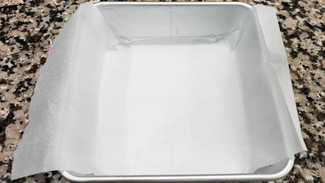 """un molde para pasteles pequeño forrado con papel pergamino """"srcset ="""" https://cdn1.zonacooks.com/wp-content/uploads/2018/08/Mile-High-Easy-Lemon-Bars-Recipe-for-Two-1. jpg 1066w, https://cdn1.zonacooks.com/wp-content/uploads/2018/08/Mile-High-Easy-Lemon-Bars-Recipe-for-Two-1-500x281.jpg 500w """"tamaños ="""" ( ancho máximo: 1066px) 100vw, 1066px"""