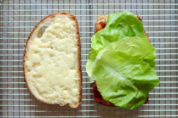 Dos rebanadas de pan con queso derretido en una y lechuga en la otra