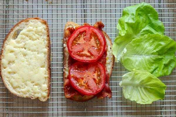 Una rebanada de pan con queso y una rebanada de pan con tocino, tomate y lechuga