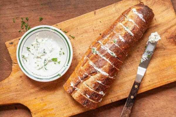 Pan de ajo casero cortado en rodajas verticales con mantequilla en el medio