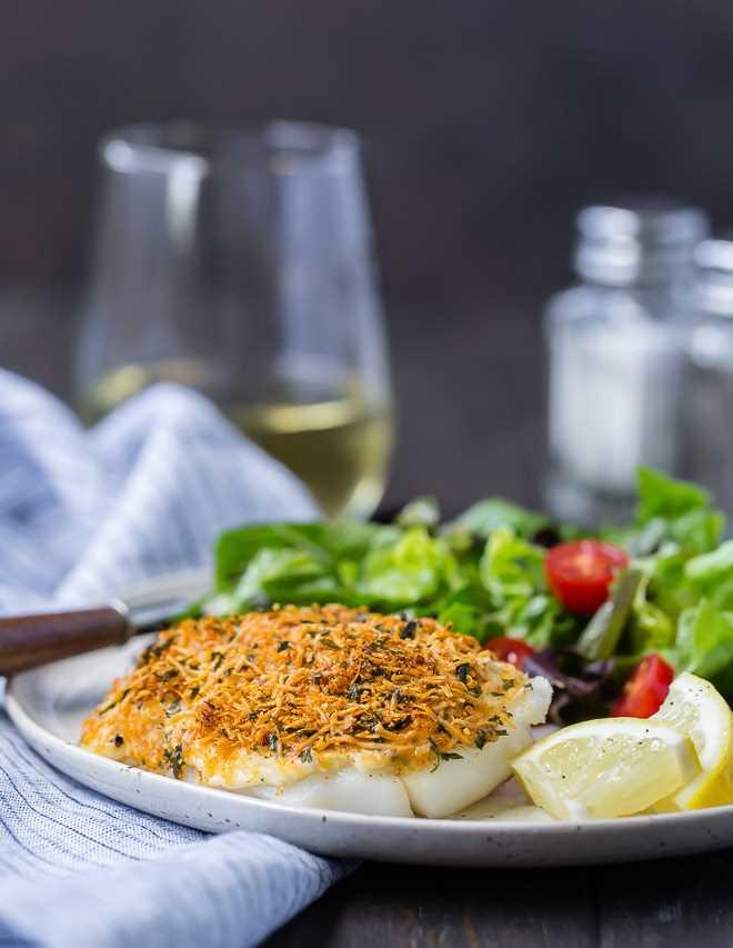 Imagen de bacalao parmesano al horno con una copa de vino en el fondo.