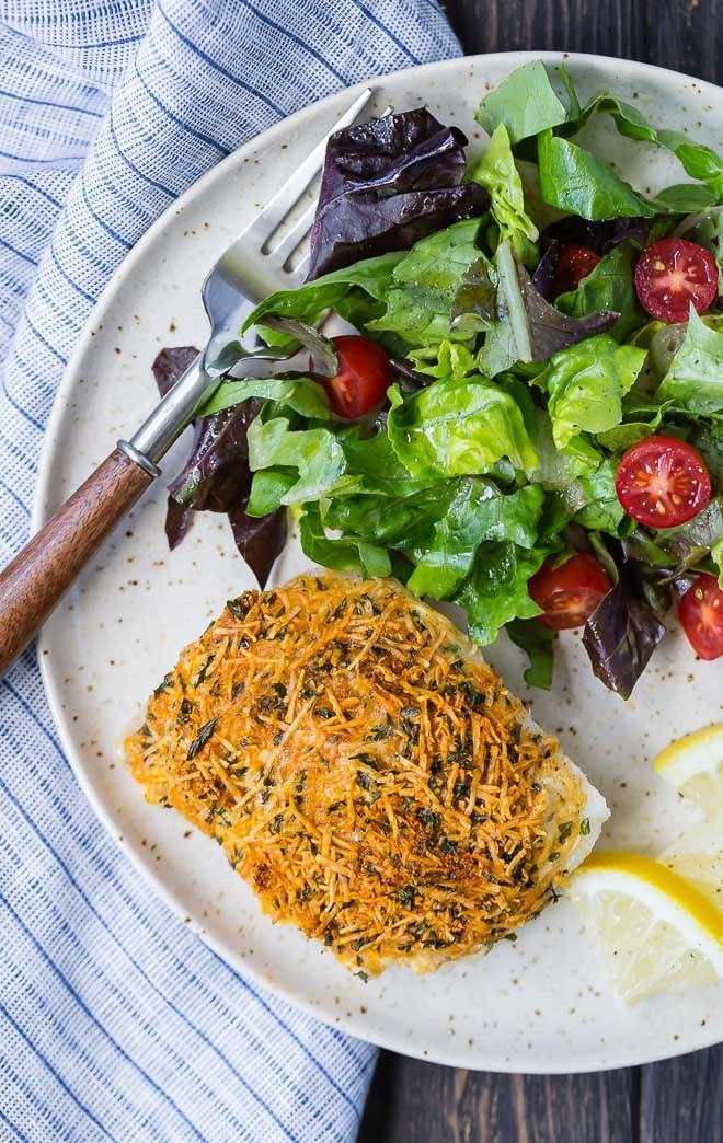 Imagen de bacalao al horno con una corteza de parmesano. Servido en un plato con una ensalada.