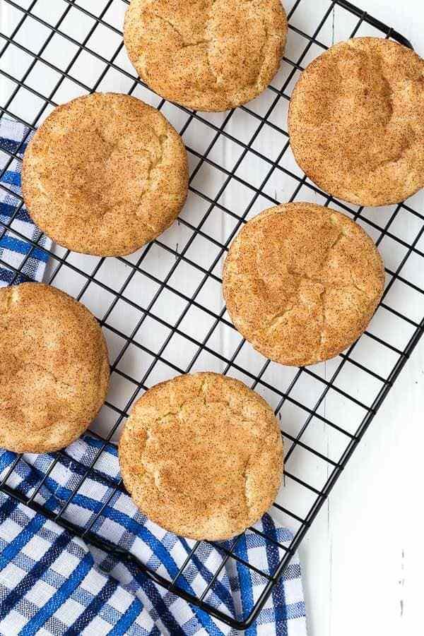 Imagen de snickerdoodles de una receta snickerdoodle; imagen tomada desde arriba, seis galletas representadas en una rejilla para enfriar con una toalla azul y blanca debajo. Disparo sobre un fondo blanco.
