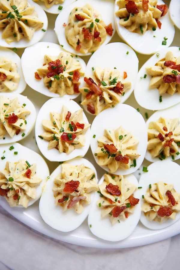 Huevos rellenos con tocino y cebollino en un plato blanco
