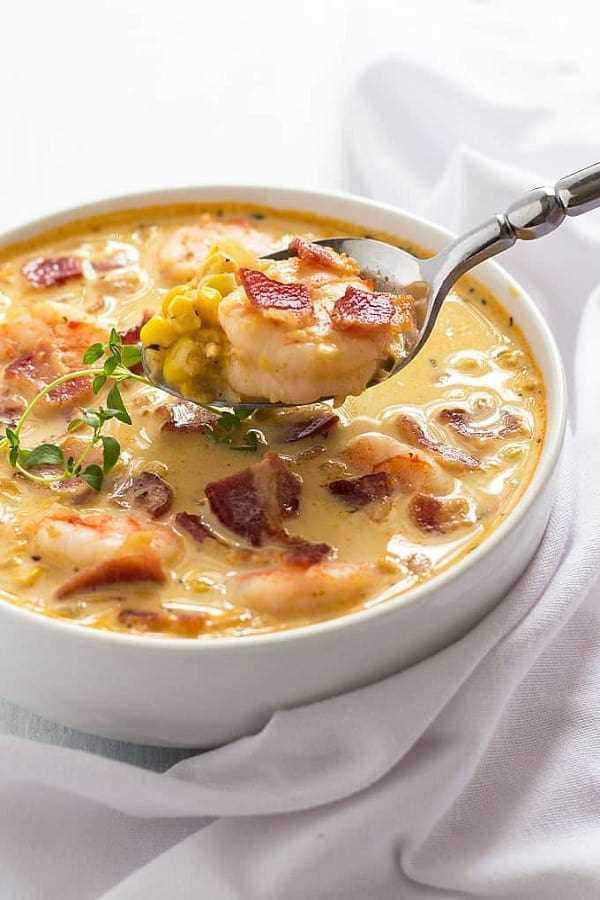 Sopa de camarones con tocino y maíz en un tazón blanco con una cuchara