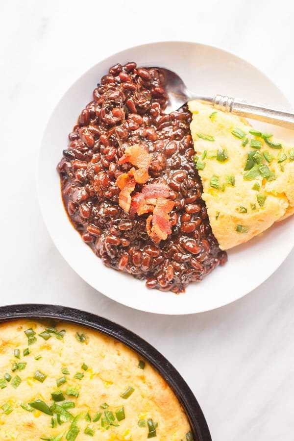 frijoles al horno con azúcar morena con tocino en un plato blanco con pan de maíz y una cuchara