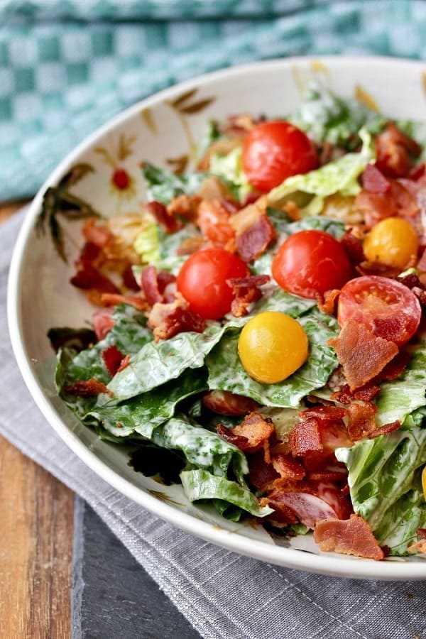 Ensalada de lechuga y tomate con tocino en un tazón blanco