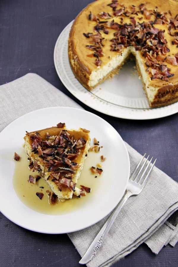 Tarta de queso de tocino y arce con una rodaja cortada en un plato blanco pequeño con un tenedor