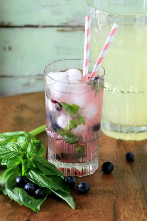 Limonada de manjericão e mirtilo em um copo com canudos rosa e brancos
