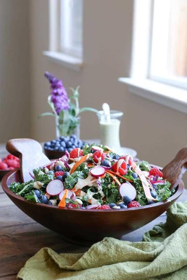 Salada de couve e mirtilo com molho vegano de soro de leite coalhado em uma tigela de madeira sobre uma mesa