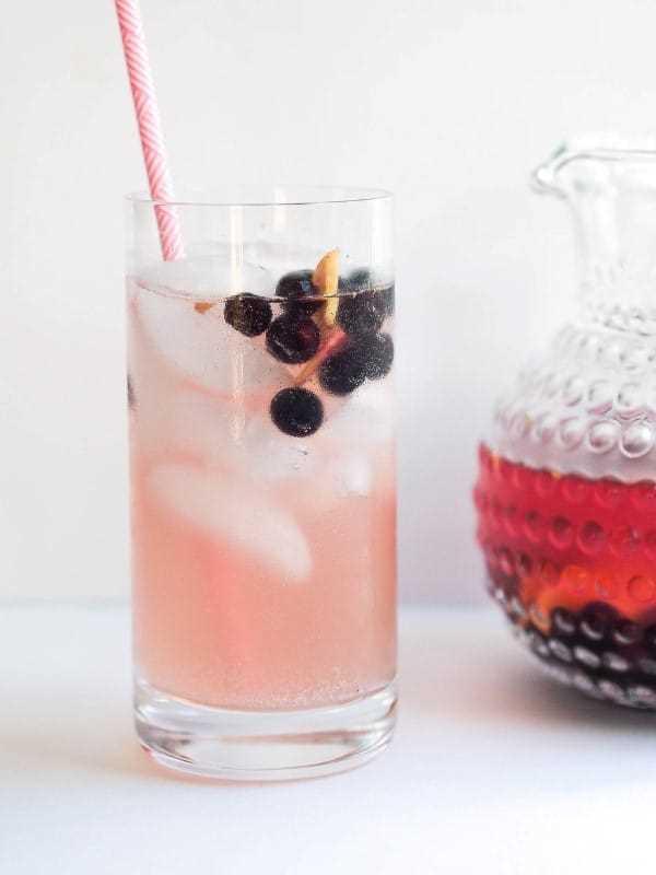 Sangria de mirtilo kombucha em um copo alto com um canudo
