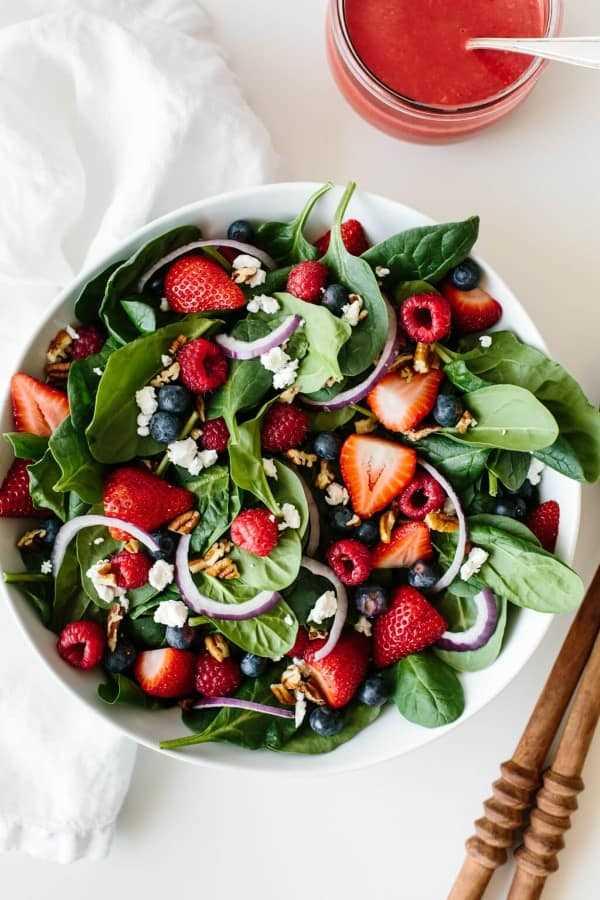 Salada de espinafre e berry em uma tigela branca com um pote de molho e uma colher