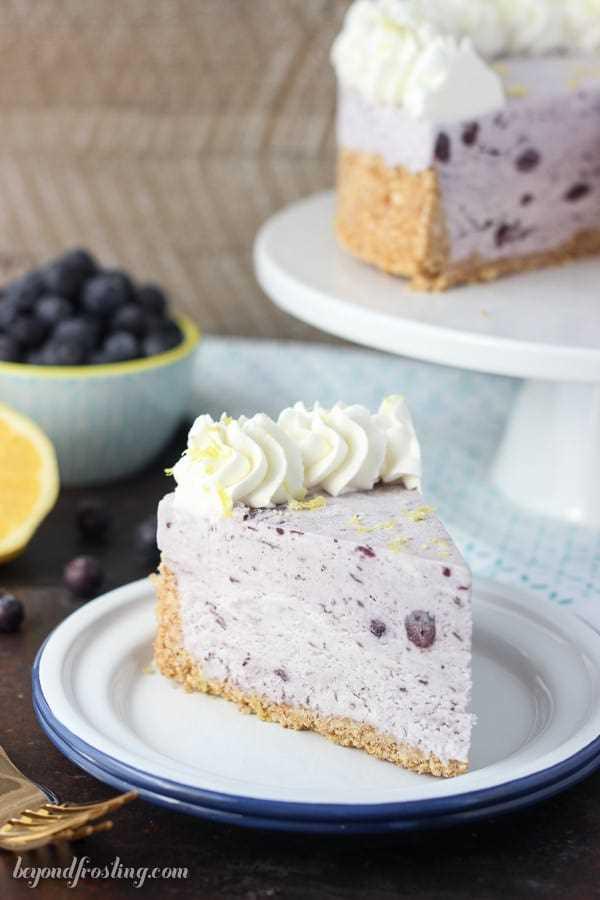 Torta de sorvete de mirtilo sem churn fácil cortado em um prato com garfos e bolo no fundo
