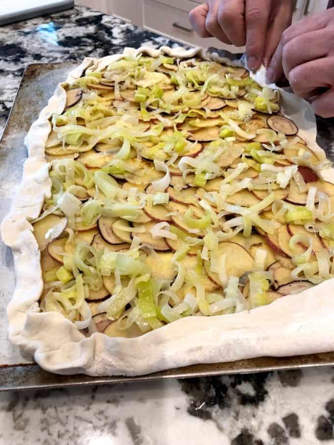 Doblar los bordes de una galette de papa con puerros en la parte superior