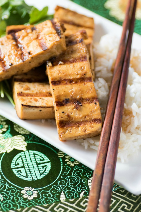 Marinated grilled spicy tofu on rice with chopsticks on a white tray