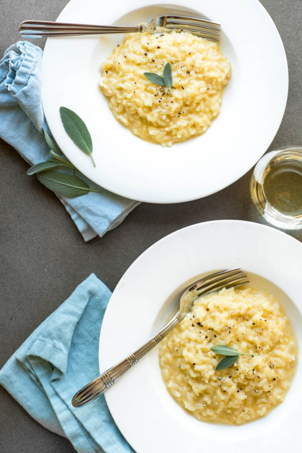 Instant cheddar cheese risotto with fresh sage in white bowls with forks