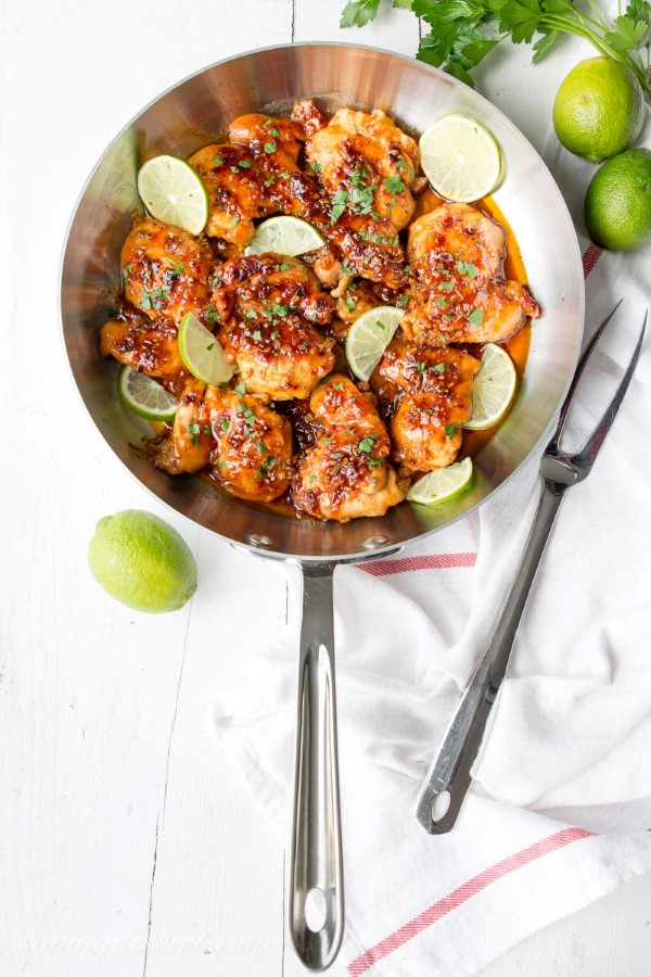 Chicken thigh recipe with honey and spicy lime in a frying pan with a white background