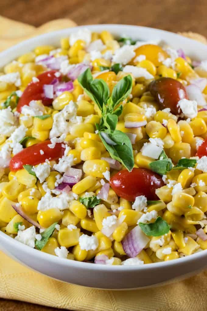 Cerca de la receta de ensalada de maíz Cotija en un tazón blanco sobre una servilleta amarilla