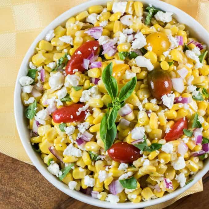 Vista aérea de la receta de ensalada de maíz Cojita en un tazón blanco con una servilleta amarilla debajo.