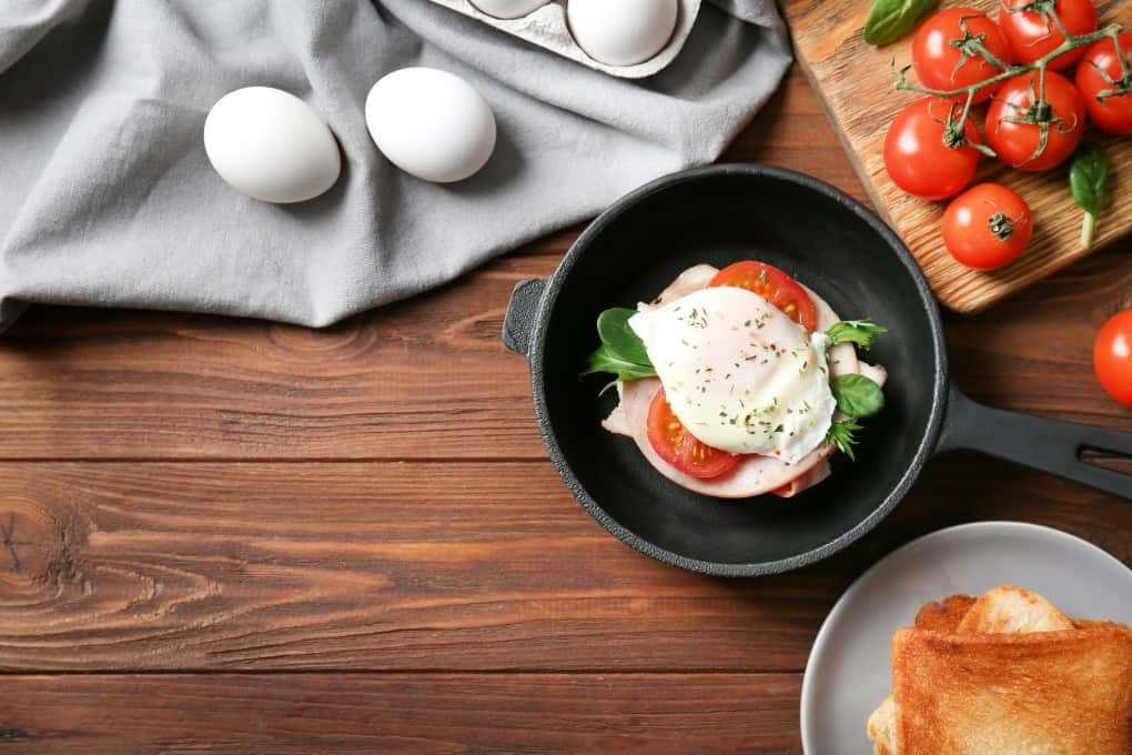 Huevos Benedicto en una pequeña sartén de hierro fundido con huevos frescos, tomates y tostadas a su alrededor.