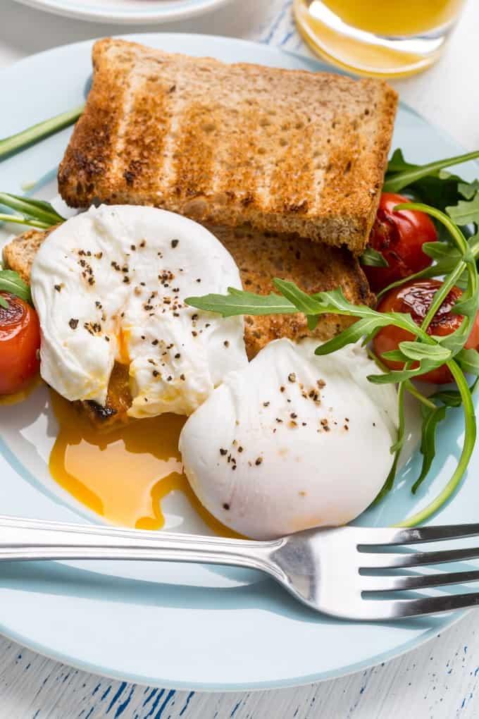 Huevos escalfados sobre tostadas en un plato azul con rúcula y tomates ampollados