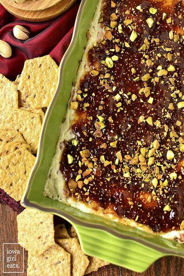Salsa tibia de higo y queso de cabra en un plato verde con galletas