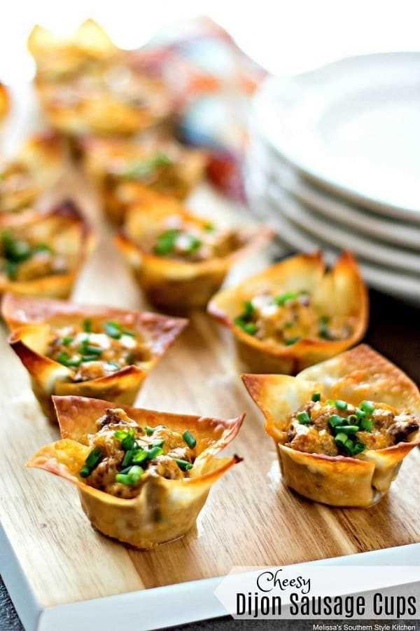 Cheesy Dijon Sausage Cups en una tabla de madera con platos blancos a un lado