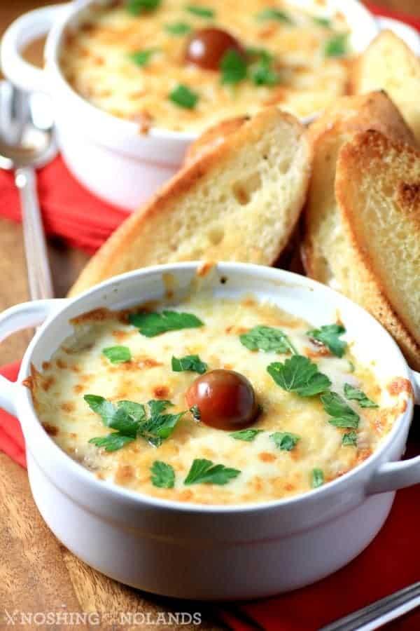 Bruschetta de pollo con queso en pequeños moldes blancos con crostinis
