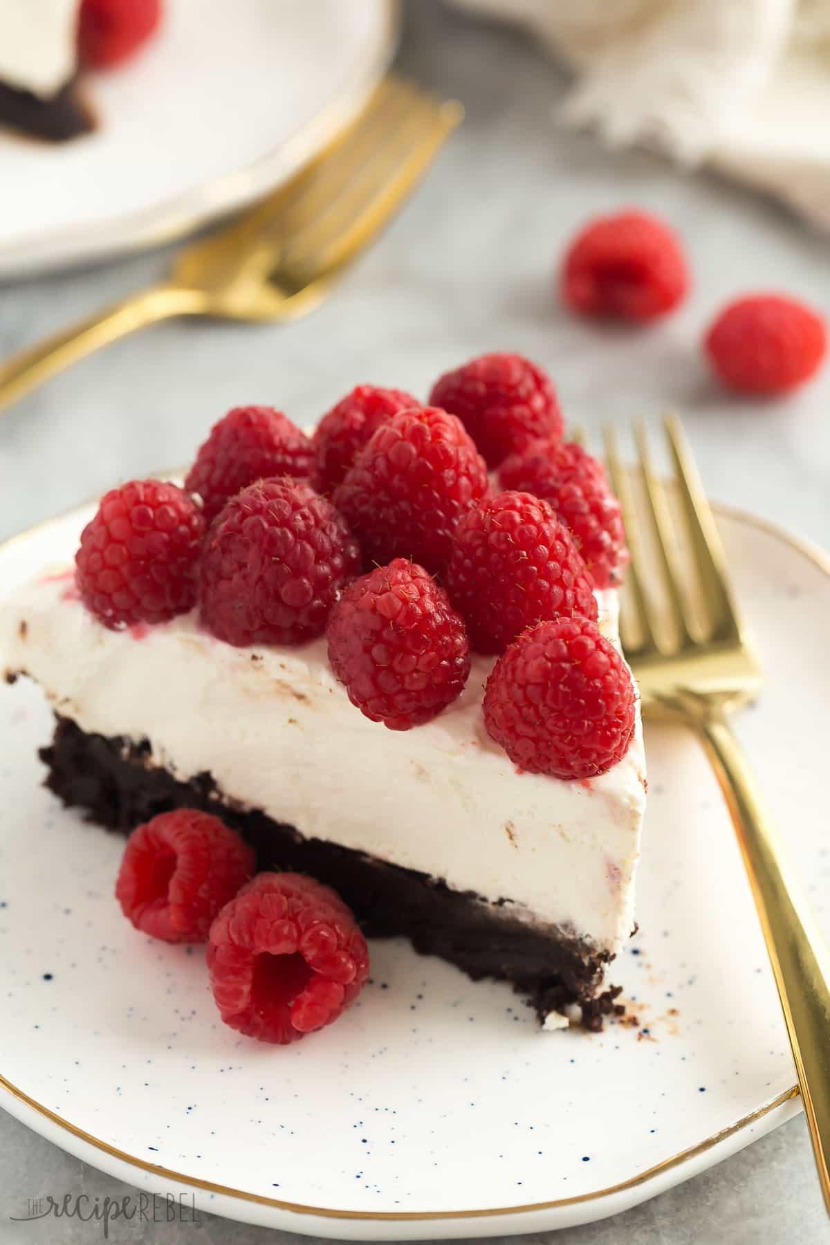 Esta tarta de queso con fondo de brownie está hecha con una base de brownie dulce, una tarta de queso suave y sin hornear sedosa y cubierta con montones de frambuesas frescas. ¡Es un elegante postre navideño que también es naturalmente libre de gluten!