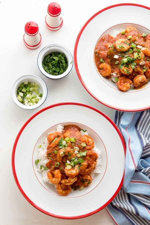Camarones picantes criollos en tazones blancos con guarnición de cebolla verde